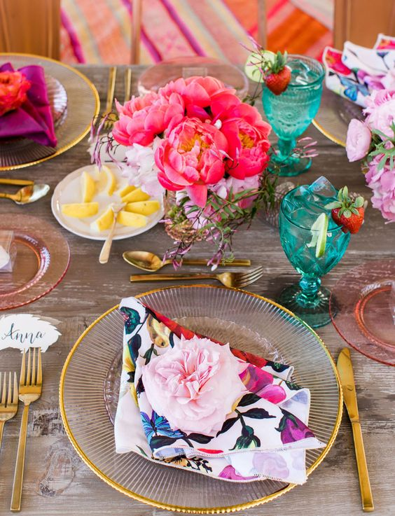 a bright bridal shower tablescape with floral print napkins, bold blooms in hot pink and pink, gold cutlery, blue glasses and pink glasses is cool