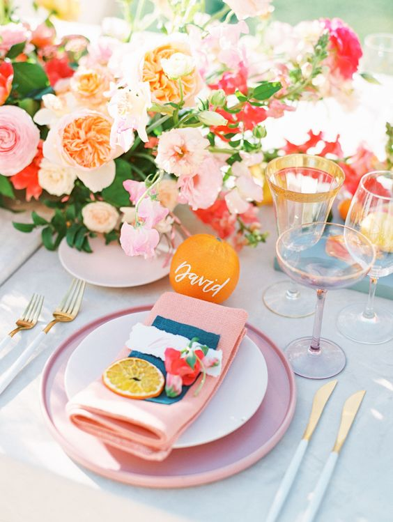 a bright bridal shower tablescape with pink plates and napkins, with pink, red and peachy blooms plus greenery, gold edge glasses