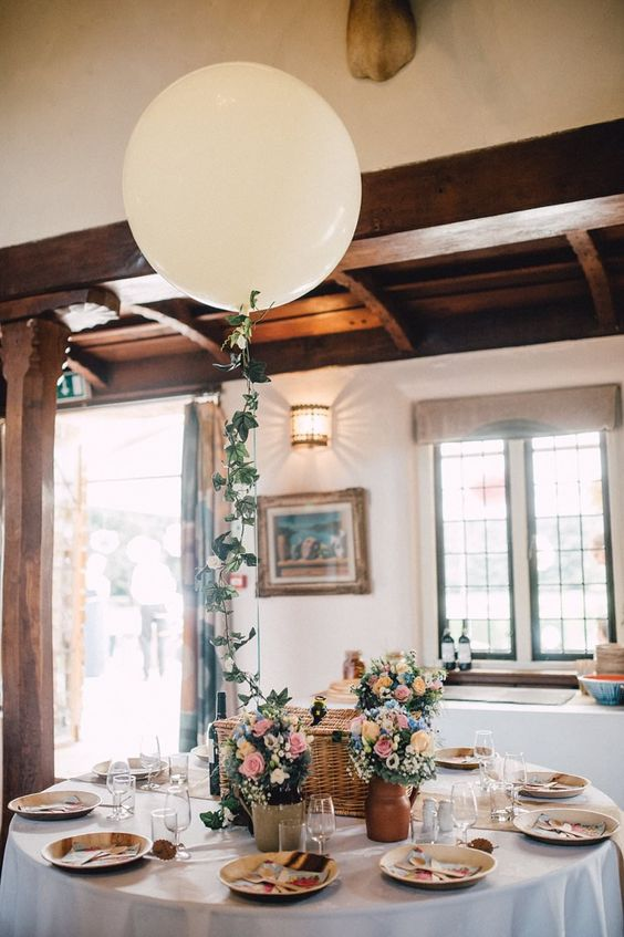 a bright wedding tablescape with a basket box, pastel blooms and greenery, a white balloon with greenery and terracotta vases
