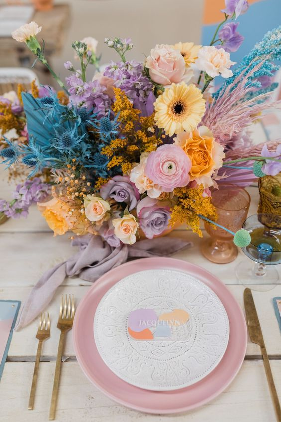 a bright wedding tablescape with an iridescent wedding floral arrangement, a pink charger, gold cutlery and colored glasses for an iridescent wedding