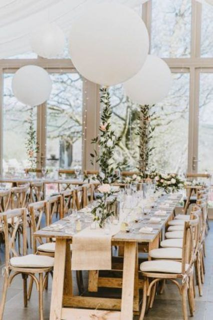 a chic farmhouse-inspired wedding reception with trestle tables and wooden chairs, burlap runners, pastel and neutral blooms and white balloons over the table
