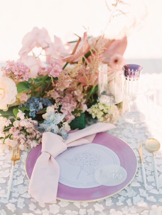 a chic iridescent wedding tablescape with a purple charger, blush, blue and lilac blooms, a clear and purple glass