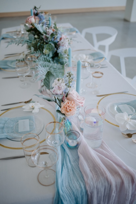 a chic iridescent wedding tablescape with turquoise and blush runners and napkins, blue candles and blue and blush florals is amazing