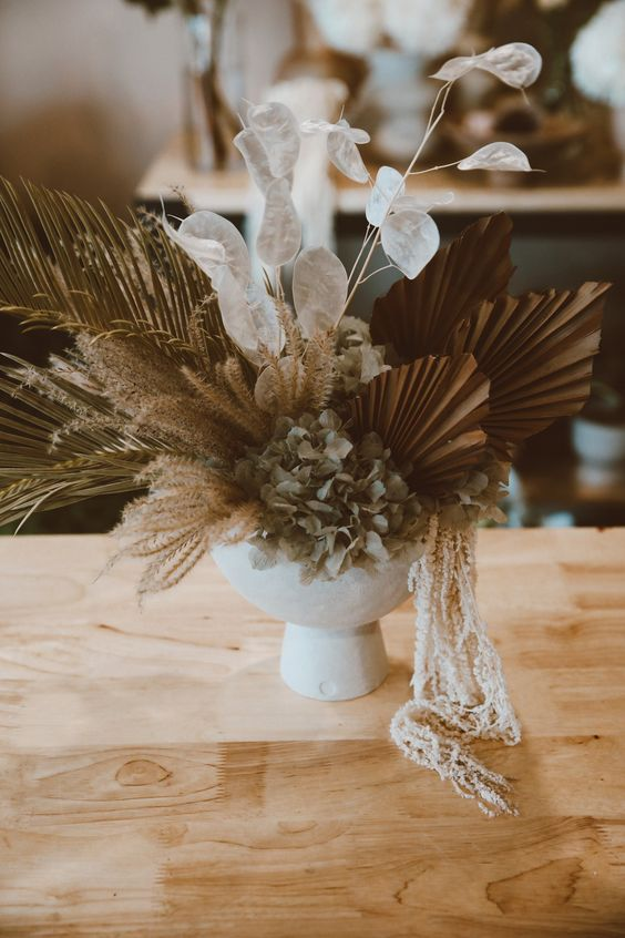 a chic wedding centerpiece of leaves, fronds, lunaria, dried hydrangeas in a white bowl is a gorgeous idea for a boho wedding
