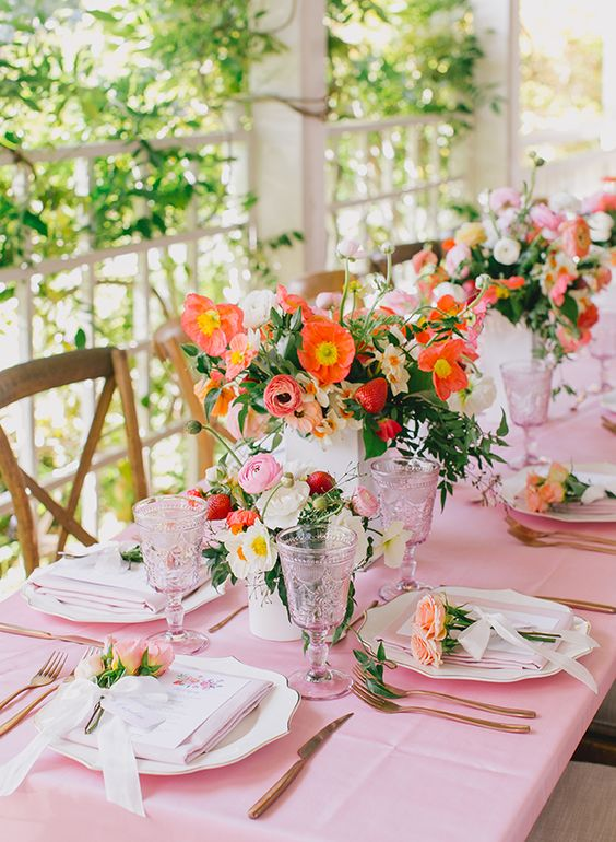 a colorful and cool bridal shower tablescape with a pink tablecloth, bold orange and pink blooms with strawberries, pink glasses is very cute
