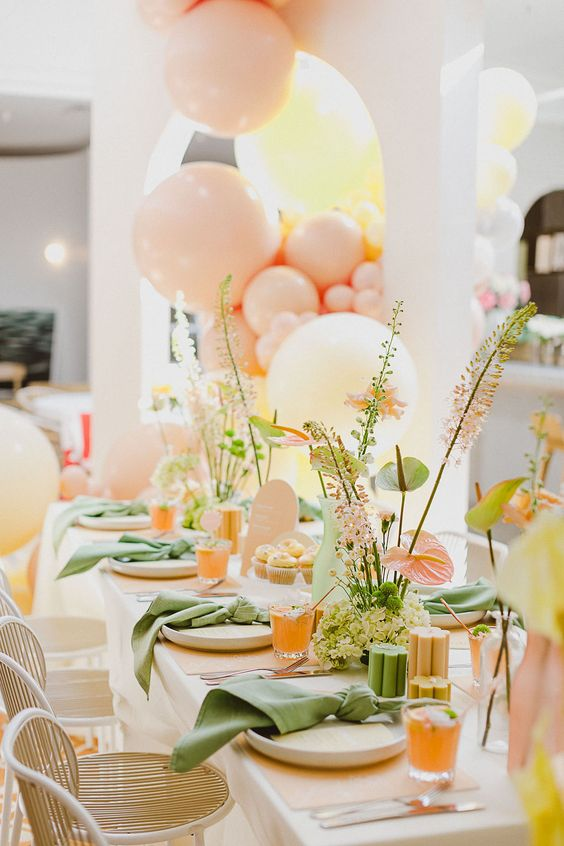 a colorful bridal shower table setting done in orange, yellow, green, pink, with lots of blooms and greenery and colorful napkins is very pretty
