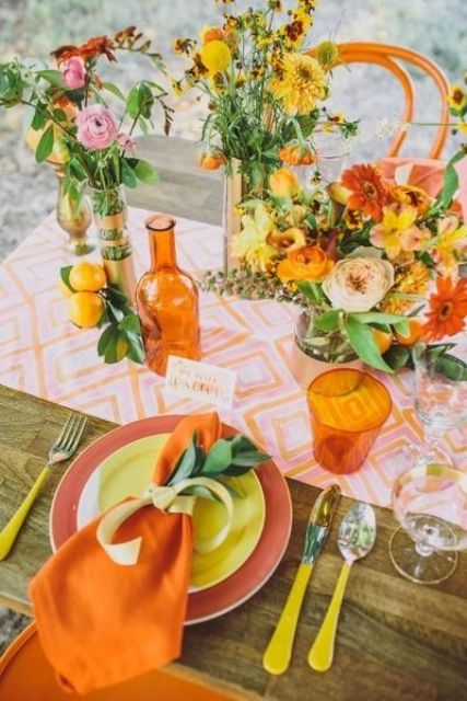 a colorful bridal shower table setting with a printed pink table runner, yellow and orange floral arrangements, a rust and a yellow plate, orange napkins and cutlery with yellow handles