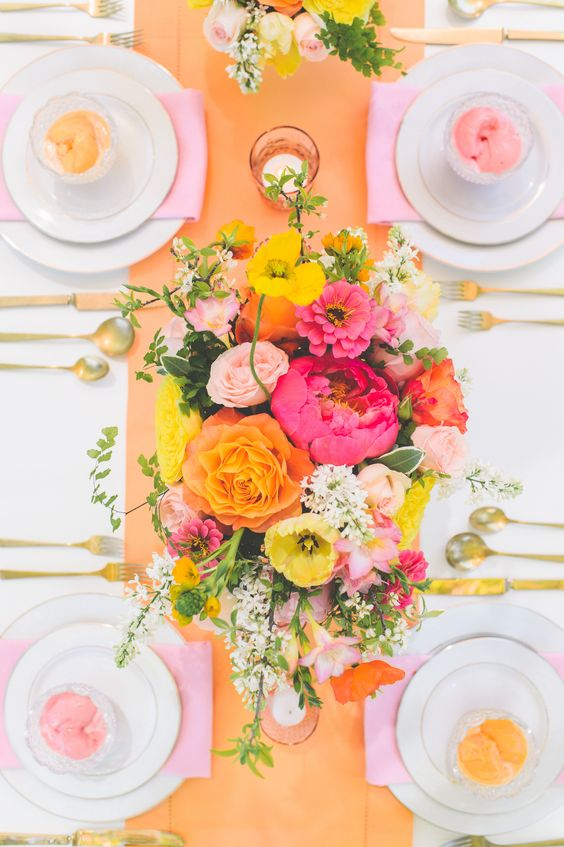 a colorful bridal shower tablescape with an orange table runner, a colorful floral centerpiece, pink napkins and colored glasses is cool