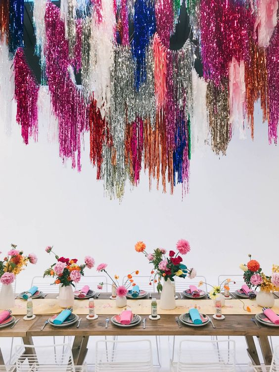 a colorful bridal shower tablescape with super bold and shiny fringe over the table, colorful blooms and greenery, colorful napkins and a neutral table runner