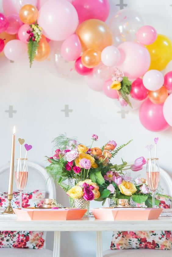a colorful bridal shower tablescape with yellow and hot pink blooms and greenery, pink chargers, a colorful balloon garland and gold candles, floral pillows