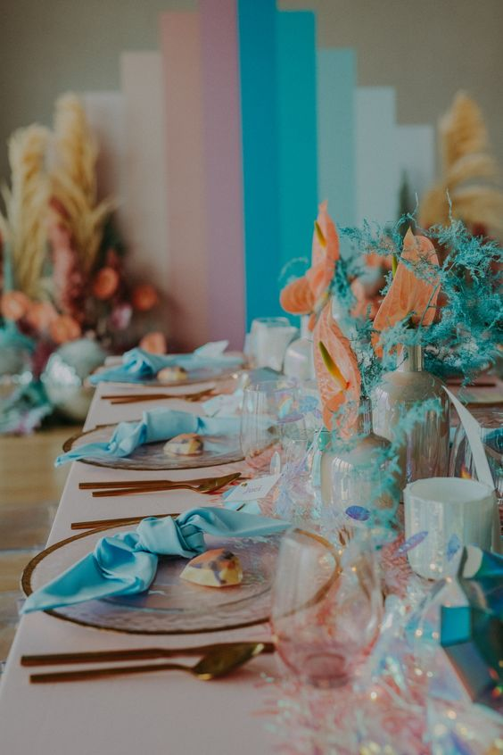 a colorful iridescent wedding tablescape with turquoise napkins, coral and turquoise blooms, blue and blush touches