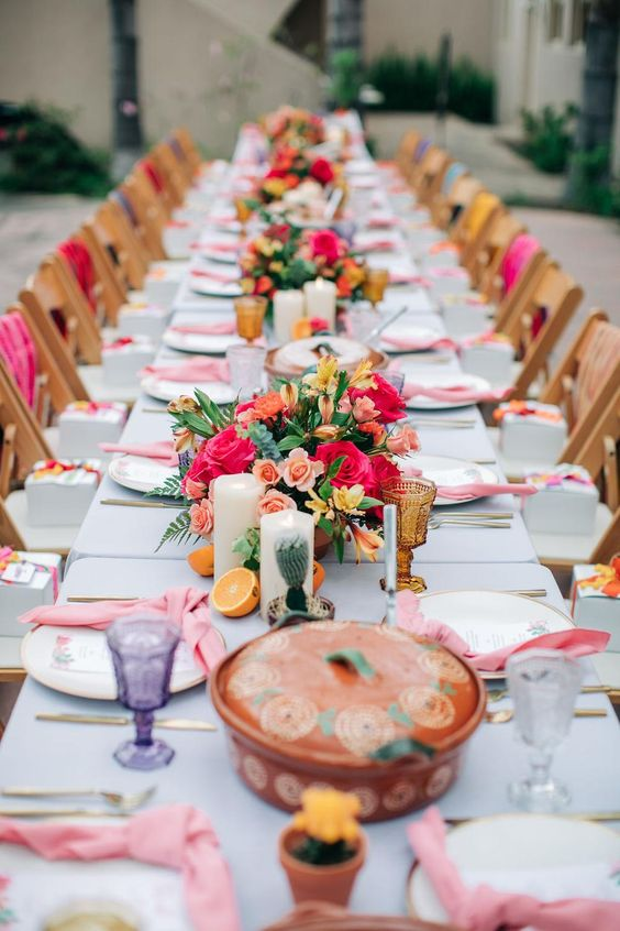 a colorful tropical bridal shower with bold blooms, citrus, candles, colored glasses and pink napkins is a lovely and fun idea
