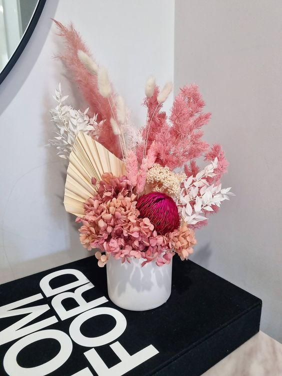 a colorful dried flower wedding centerpiece with hydrangeas, fronds, leaves and pampas gras splus bunny tails will make a statement with its color