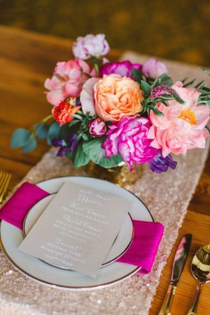 a cool and bold bridal shower place setting with a pink sequin runner, hot pink and light pink floral centerpiece, a fuchsia napkin and gold cutlery