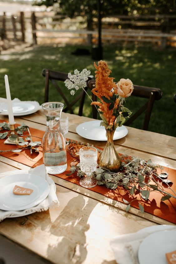a cool and simple fall boho wedding centerpiece of a gilded vase, a blush rose, white and rust blooms, greenery on the table and a rust-colored table runner