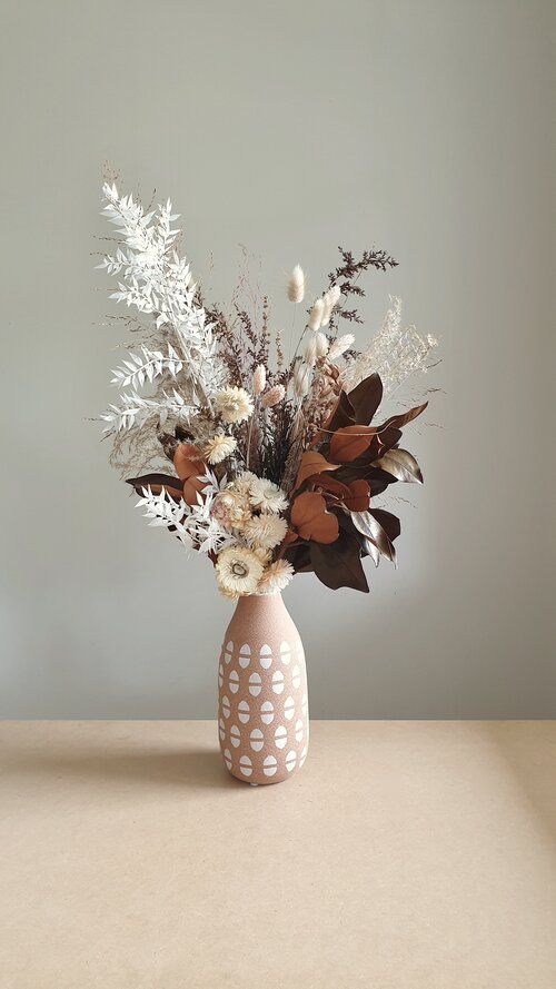 a cool wedding centerpiece of dried blooms, leaves, grasses placed into a printed pink vase is a cool idea for a fall boho wedding