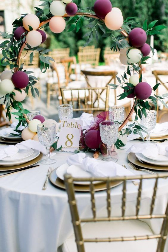 a creative and playful wedding centerpiece of a copper hoop with purple and blush balloons and greenery is a very fresh idea