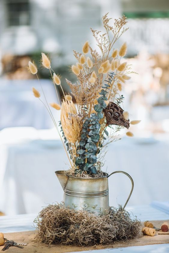 a creative wedding centerpiece of a metal jug, bunny tails, eucalyptus and lotus is a very non-traditional arrangement to rock in the fall