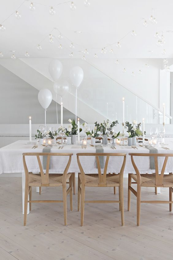 a delicate and minimalist wedding tablescape with white blooms and greenery, candles, grey porcelain and white balloons is wow