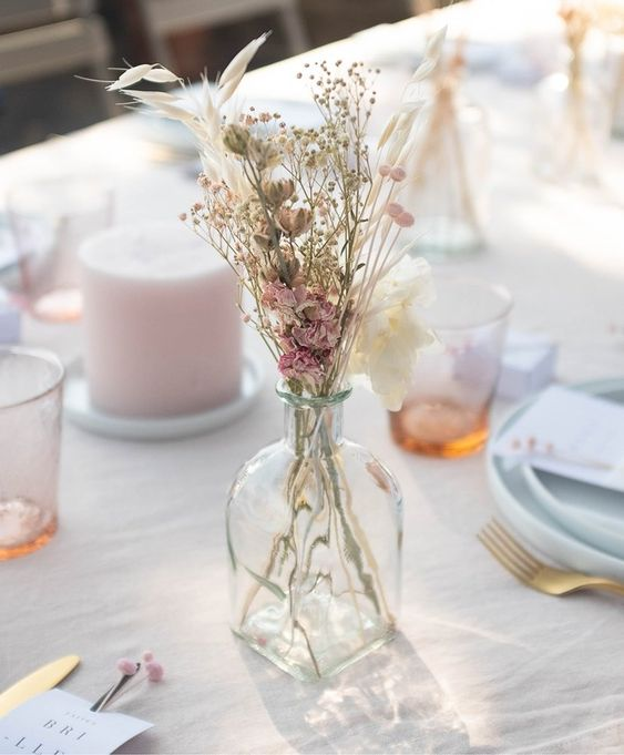 a delicate dried flower centerpiece of a bottle with dried pink blooms and some grass is a chic solution for a spring wedding
