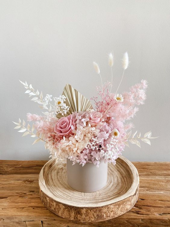 a delicate wedding centerpiece with dried and fresh roses, daisies, hydrangeas, bunny tails, fronds and leaves is amazing