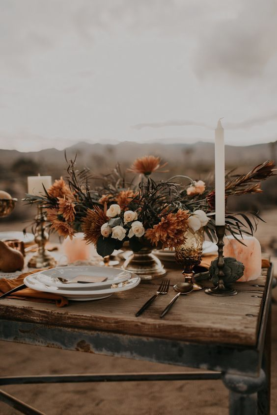 a fall boho wedding centerpiece of a gilded bowl, neutral and rust-colored blooms and greenery, candles is a lovely idea