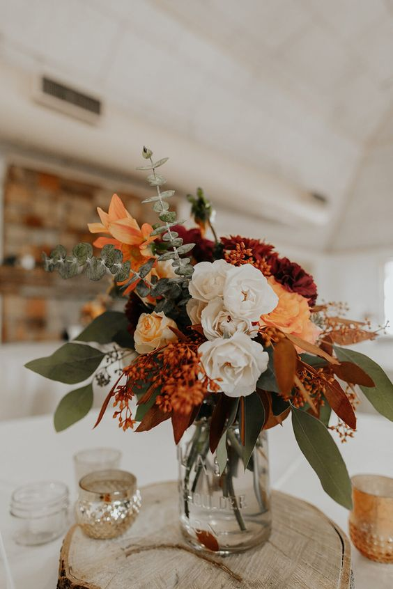 a fall boho wedding centerpiece of a wood slice, a jar with white, rust and burgundy blooms, greenery and fall leaves is amazing