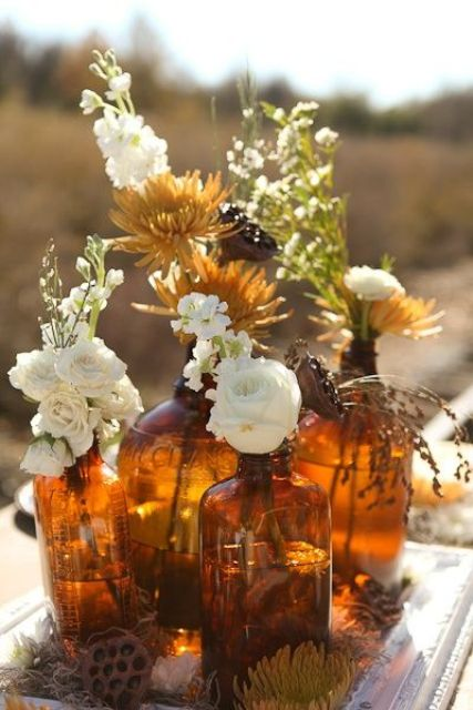 a fall boho wedding centerpiece of apothecary bottles, white and rust blooms and greenery, lotus and dried grasses is cool and relaxed