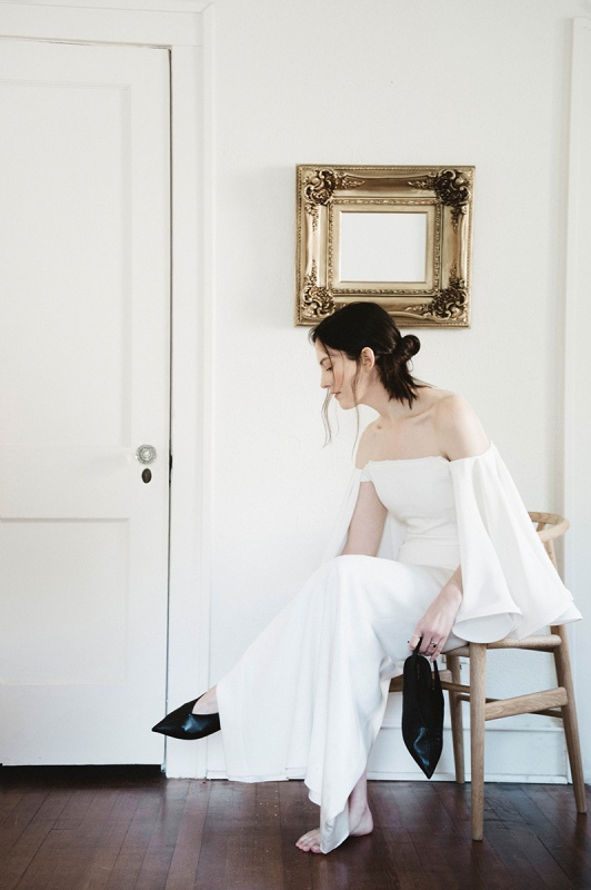 a fantastic modern off the shoulder wedding dress with bell sleeves and vintage-inspired black pointed toe shoes