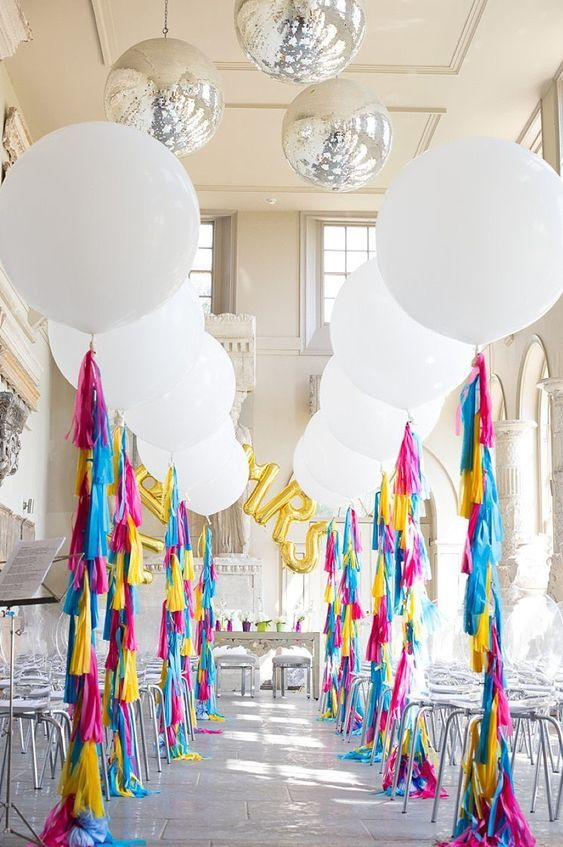 a fun and colorful wedding ceremony space with white balloons and colorful tassels, with gold balloon letters and sheer chairs