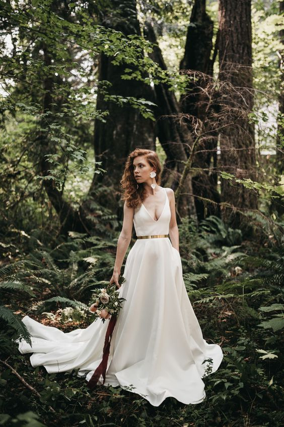 a gorgeous plain A-line wedding dress with a depe neckline, a shiny metallic belt and a pleated skirt with a long trian plus floral earrings