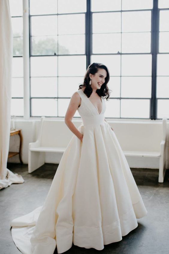 a gorgeous plain wedding ballgown with thick straps, a deep neckline and a pleated skirt with pockets and a train plus vintage statement earrings
