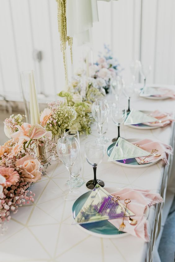 a holographic wedding tablescape with an ombre floral table runner, gold fringe, iridescent chargers and triangle menus, pink napkins