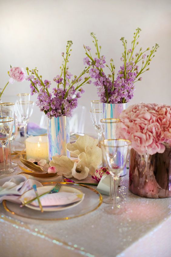 a holographit wedding table setting with a white sequin tablecloth, a clear charger, lilac and pink blooms and gold cutlery