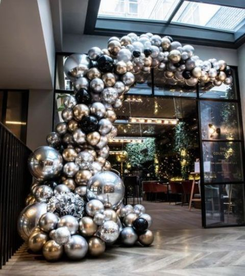 a jaw-dropping silver, gold and black balloon garland over the entrance to the wedding reception space is a gorgeous idea