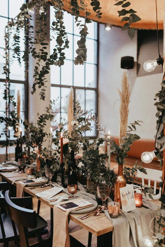a lively and cool boho wedding centerpiece of copper bottles with pampas grass and eucalyptus is a very fresh idea suitable for all the seasons