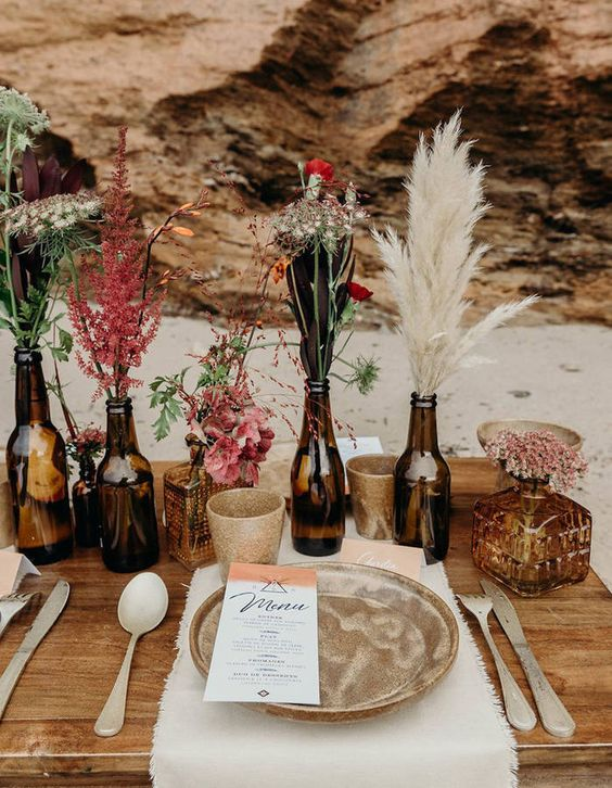 a lovely and simple fall boho cluster wedding centerpiece of beer bottles, with pampas grass, bold blooms, greenery and wildflowers plus candleholders around