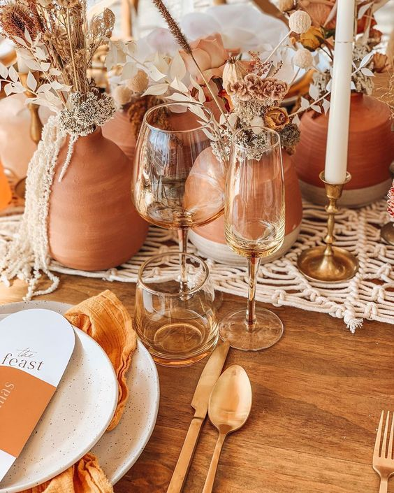 a lovely boho fall wedding centerpiece of terracotta vases, dried blooms, foliage and leaves plus a macrame runner is gorgeous and veyr trendy