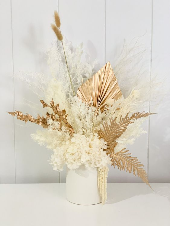 a lovely dried flower wedding centerpiece of gilded leaves, fronds, bunny tails, white blooms and white grasses is a gorgeous idea