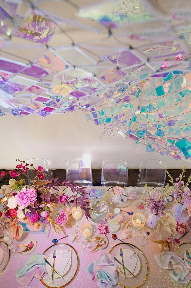 a lovely iridescent wedding reception space with a holographic panel on the wall, a pink sequin tablecloth, pink, blush, fuchsia blooms, candles, clear chargers