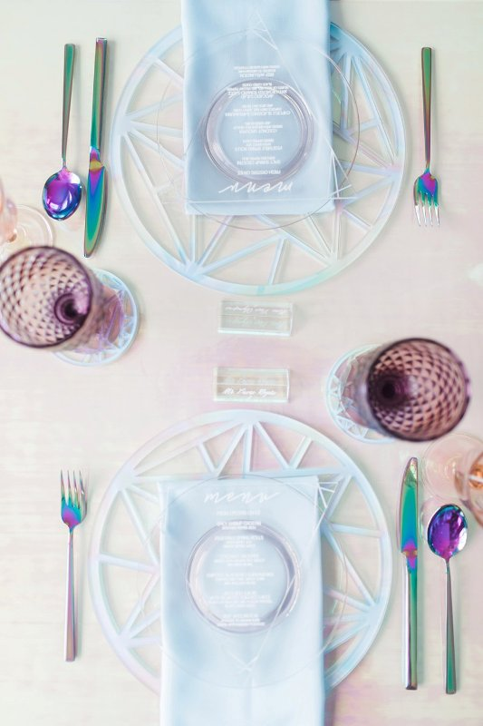 a lovely modern iridescent wedding tablescape with catchy chargers, blue napkins, holographic cutlery, purple glasses is wow