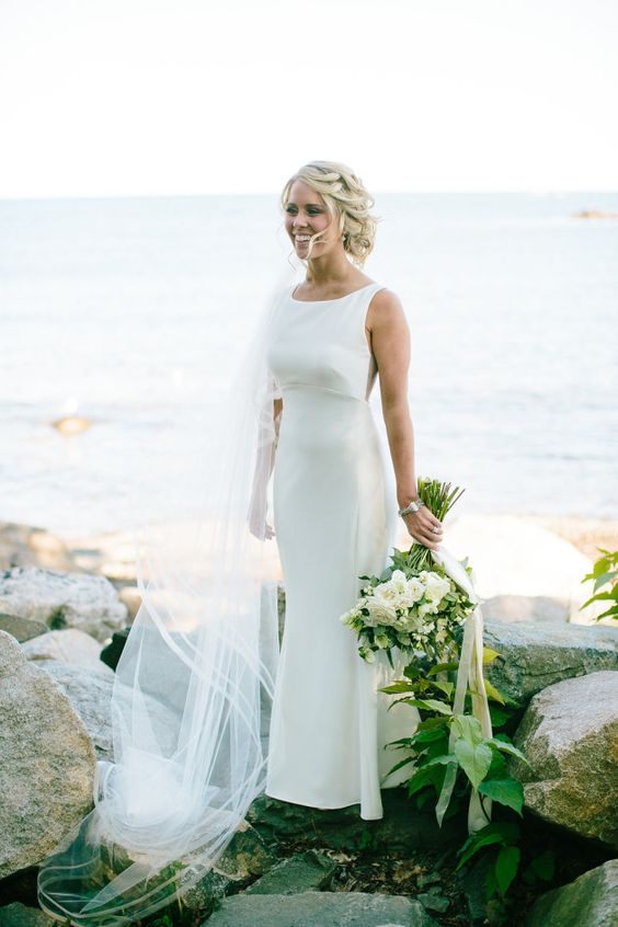 a lovely modern mermaid sleeveless wedding dress with an empire waist and a high neckline plus a cathedral veil for a tropical bride