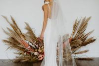 a lovely modern plain wedding dress on straps, with an open back and a small train, with a long cathedral veil is an amazing idea