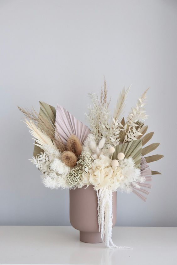 a lovely pastel wedding centerpiece in a dusty pink vase, with neutral and pink fronds, grasses, billy balls, dried white leaves is cool