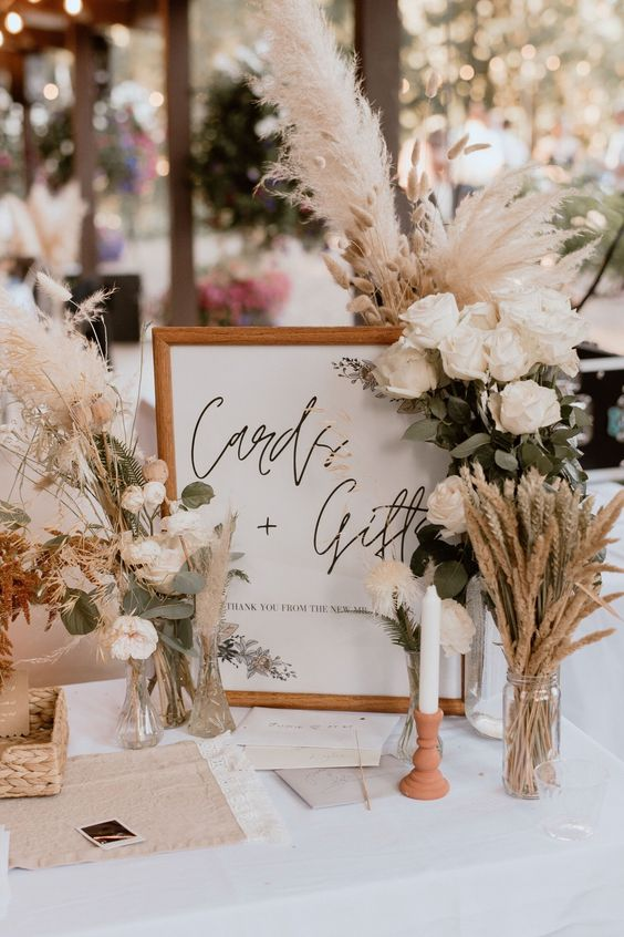 a lovely summer or fall boho wedding centerpiec eof white roses, pampas grass, wheat, candles and a neutral sign is a very cool idea for a boho space