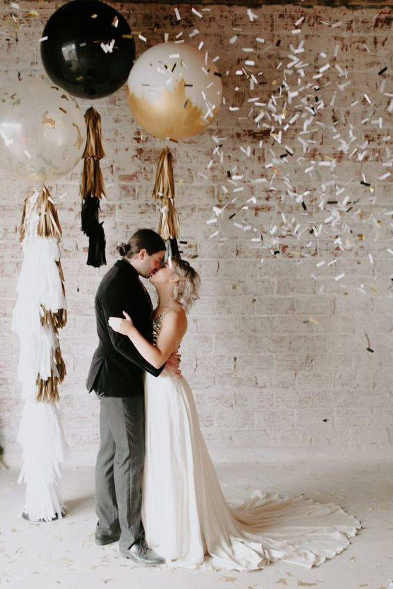 a lovely wedding ceremony space with a clear, black and gold balloon with tassels is a lovely and cool modern idea