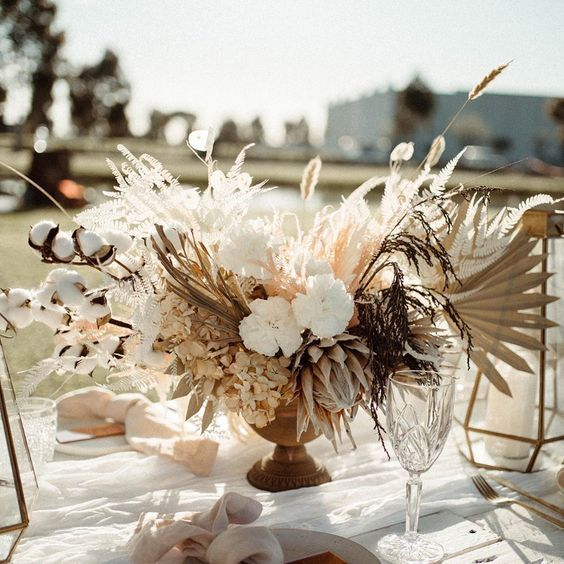 a lush and lovely wedding centerpiece of white fresh and dried blooms, fronds, grasses, cotton and bunny tails is a pretty idea