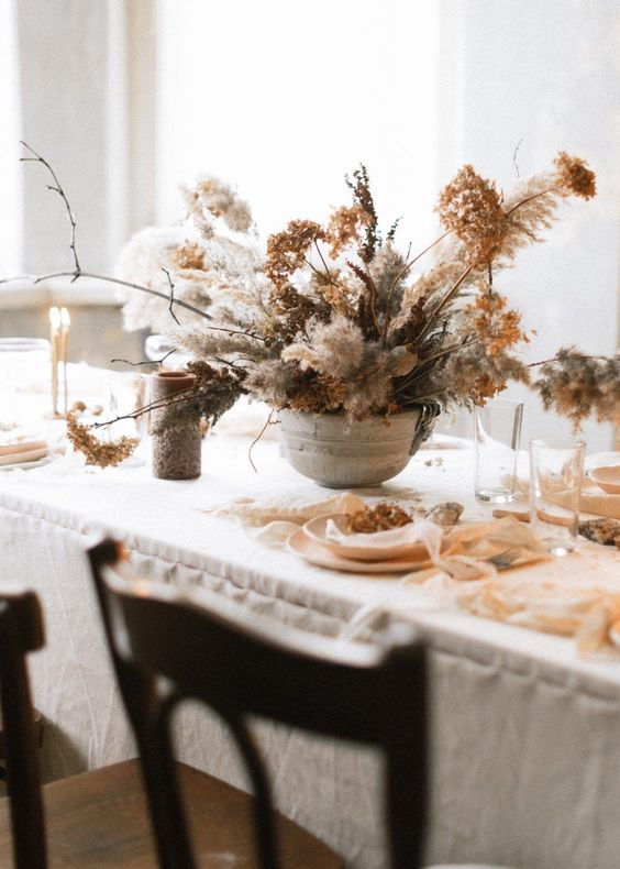 a lush and wild-looking wedding centerpiece fully made of dried blooms, grasses and twigs in a grey bowl is a beautiful idea for a non-traditional wedding