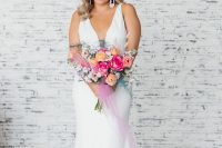 a minimalist mermaid wedding dress with a covered plunging neckline and statement earrings and a train plus statement earrings