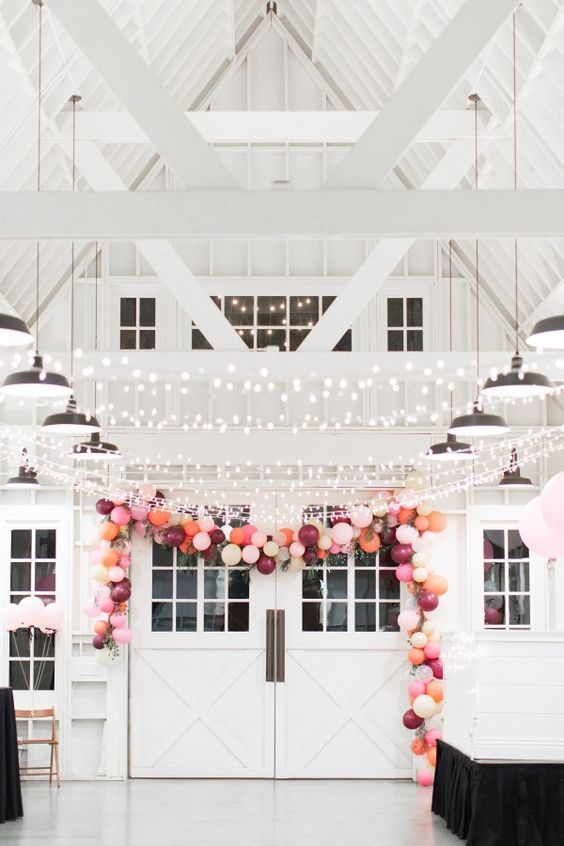 a modern farmhouse wedding venue styled with lights and with a colorful balloon garland is a lovely and playful space to tie the knot
